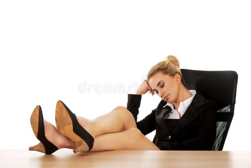 Jeune femme d'affaires fatiguée tenant des jambes sur le bureau image stock