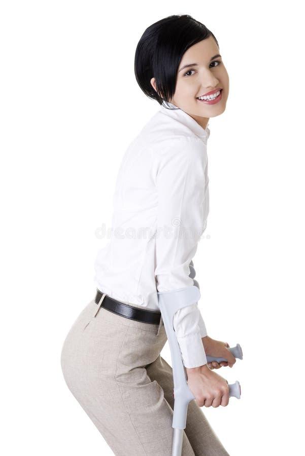 Jeune femme d'affaires heureuse avec des béquilles images stock