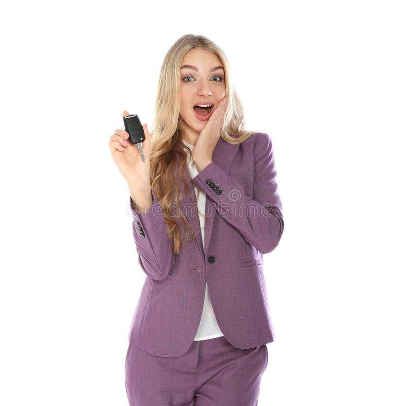 Jeune femme d'affaires heureuse avec la clé de voiture sur le fond blanc photographie stock