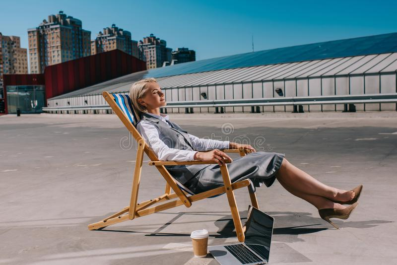 jeune femme d'affaires heureuse dans le tenue de soirée détendant dans le canapé du soleil photo libre de droits