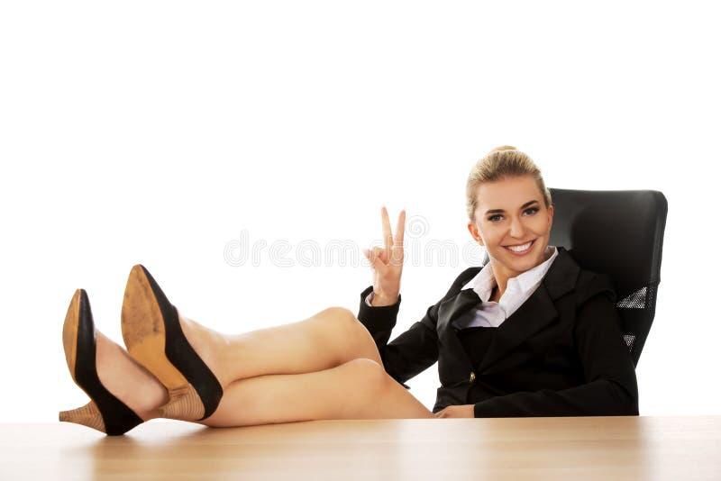 Jeune femme d'affaires heureuse tenant des jambes sur le bureau photographie stock libre de droits