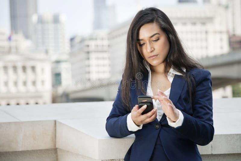 Jeune femme d'affaires indienne à l'aide du téléphone intelligent photos libres de droits