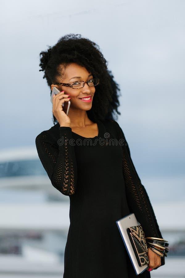 Jeune femme d'affaires ? la mode ? l'aide du t?l?phone portable photo stock