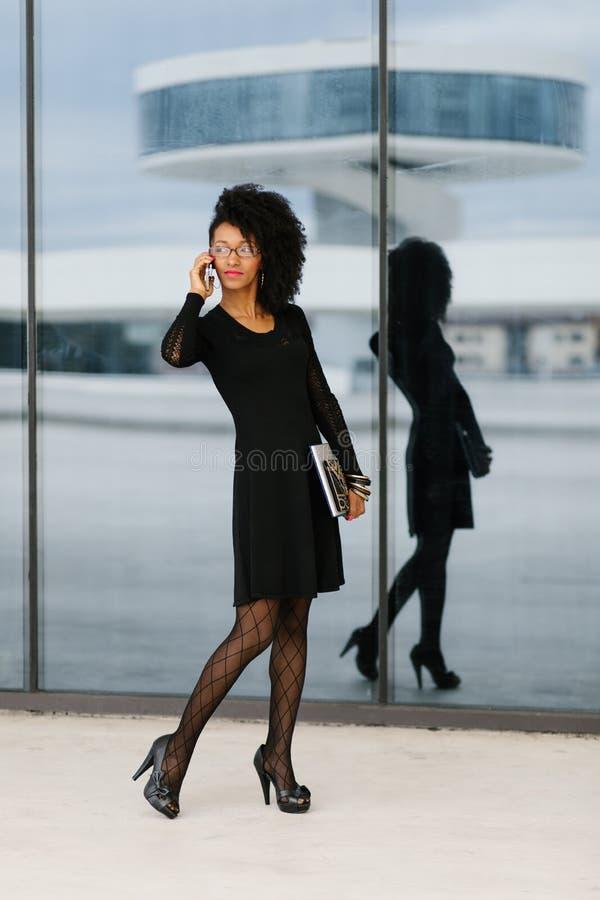 Jeune femme d'affaires ? la mode ? l'aide du t?l?phone portable photo libre de droits