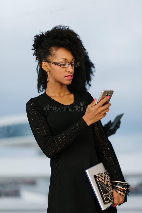 Jeune femme d'affaires ? la mode ? l'aide du t?l?phone portable image stock