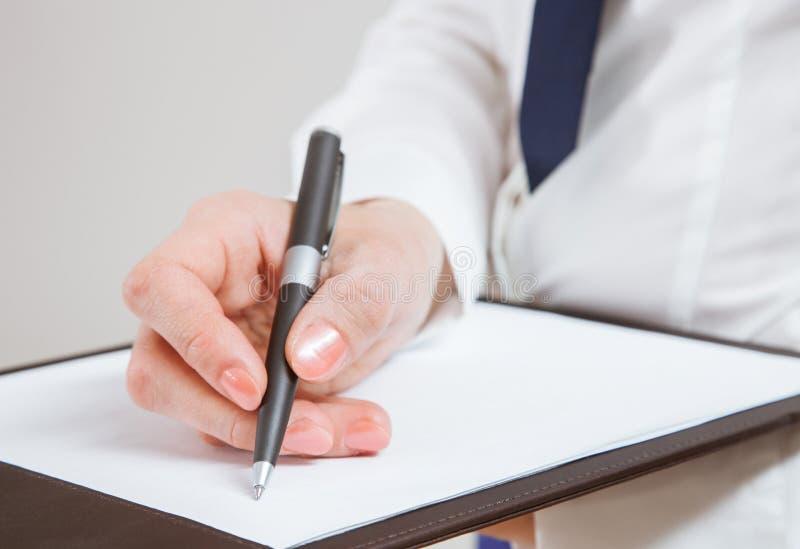 Jeune femme d'affaires méconnaissable tenant des documents et un stylo image stock