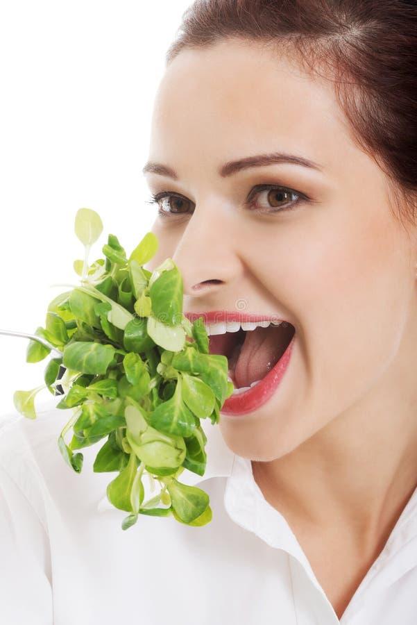 Jeune femme d'affaires mangeant de la laitue. image stock