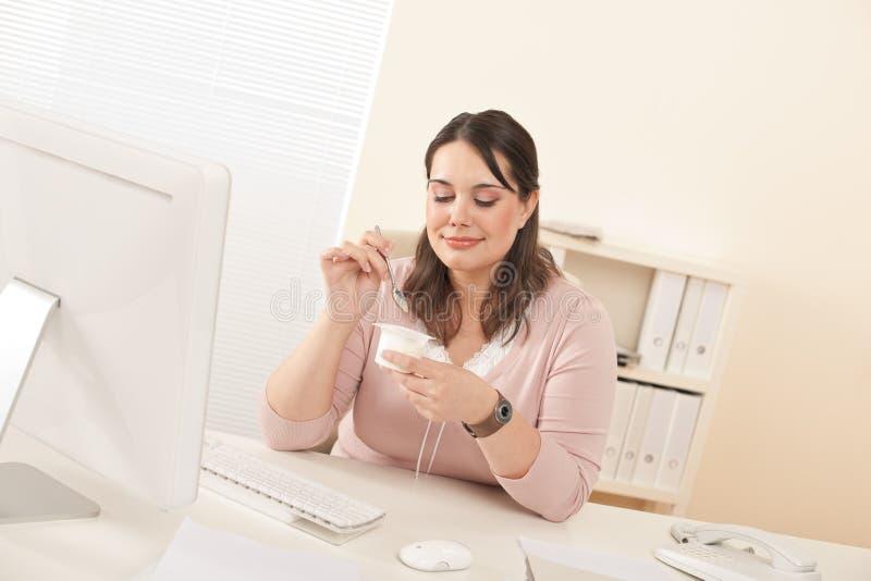Jeune femme d'affaires mangeant du yaourt au bureau photographie stock