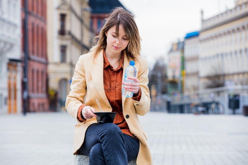Jeune femme d'affaires mangeant la salade et l'eau potable  images stock