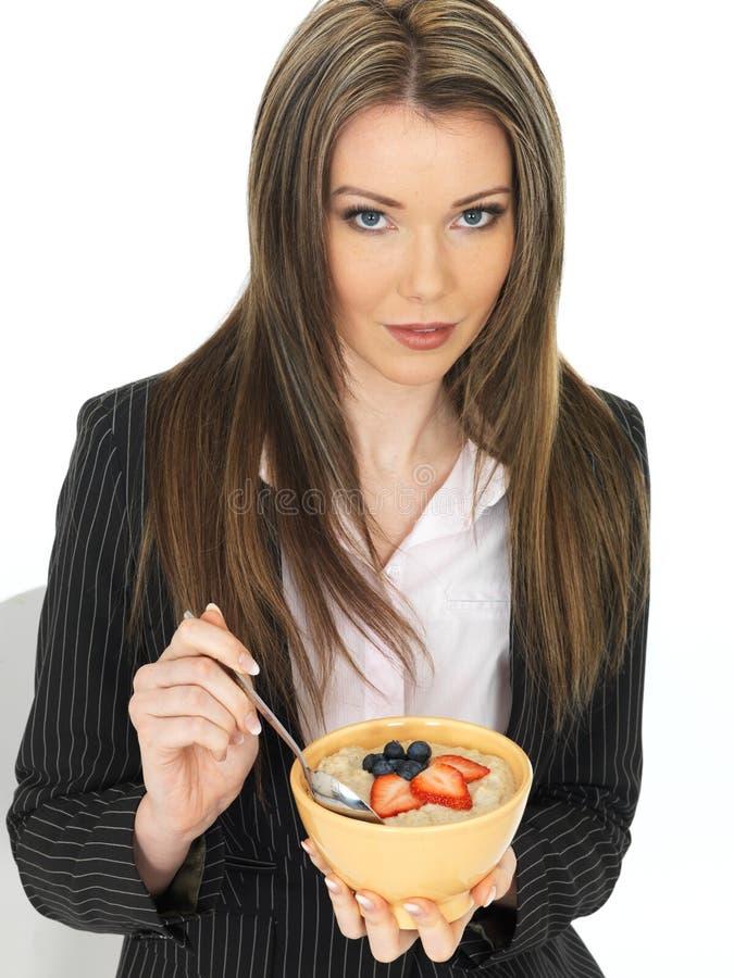 Jeune femme d'affaires mangeant un bol de gruau avec le fruit frais image libre de droits