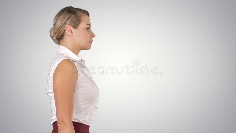 Jeune femme d'affaires marchant sur le fond de gradient photo stock