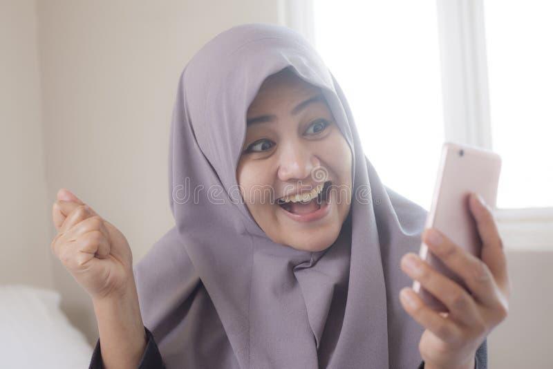 Jeune femme d'affaires musulmane Get Good News ? son t?l?phone photographie stock libre de droits