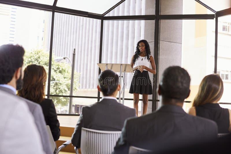 Jeune femme d'affaires noire présent le séminaire à une assistance photos stock