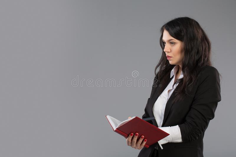 Jeune femme d'affaires notant des notes au bloc-notes Écriture assez réfléchie de dame d'affaires sur le presse-papiers se tenant images stock