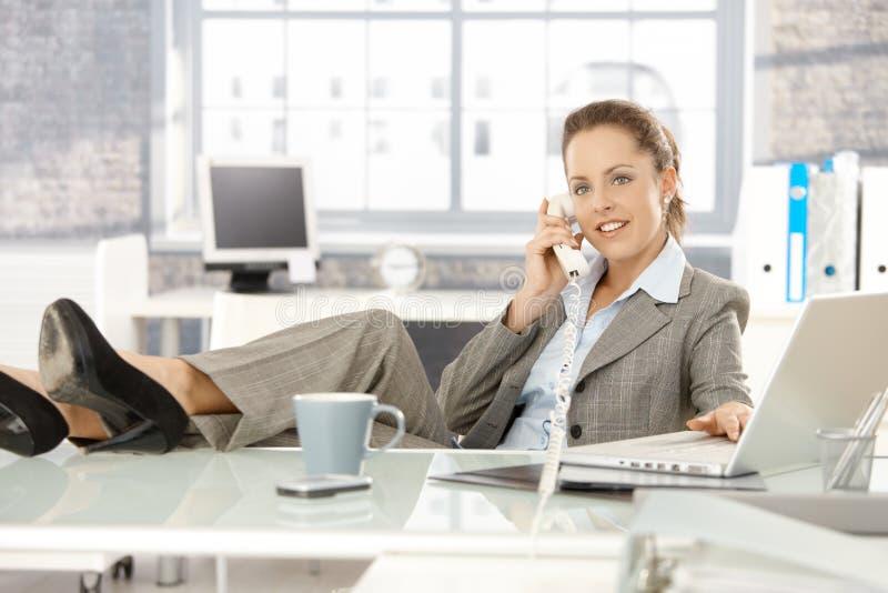 Jeune femme d'affaires parlant au téléphone dans le bureau photos stock