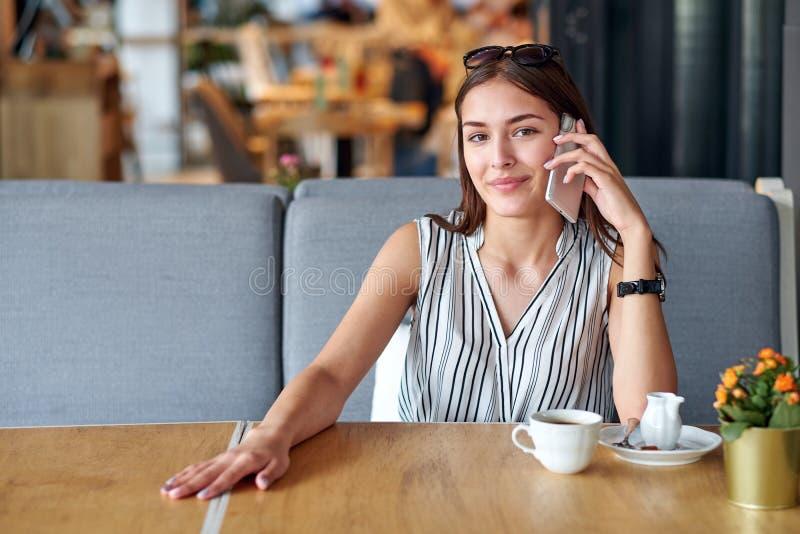 Jeune femme d'affaires parlant au t?l?phone dans le caf? image stock