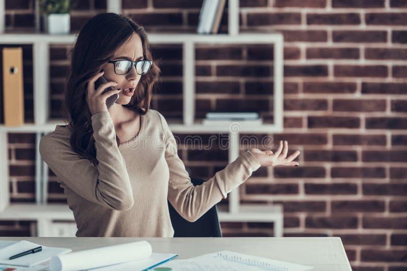 Jeune femme d'affaires parlant sur le téléphone portable à la maison photo stock