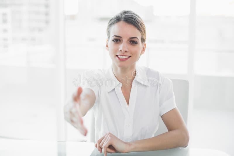 Jeune femme d'affaires polie atteignant sa main à l'appareil-photo images stock