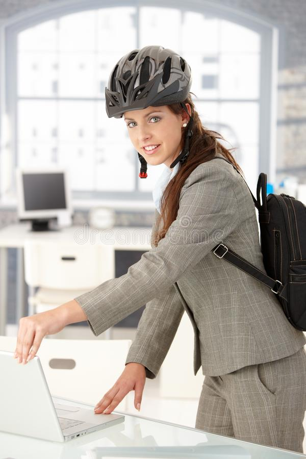 Jeune femme d'affaires quittant le bureau par le sourire de vélo photos stock