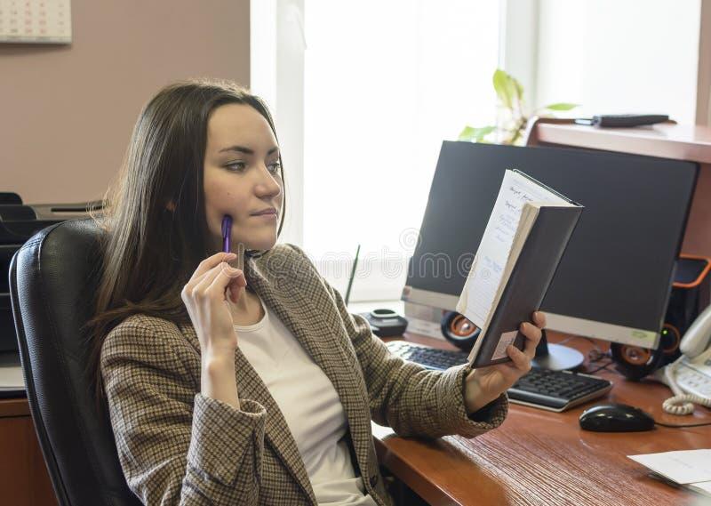 Jeune femme d'affaires réfléchie attirante faisant des notes en bloc-notes sur le fond de bureau photo libre de droits