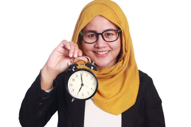Jeune femme d'affaires retenant une horloge images libres de droits