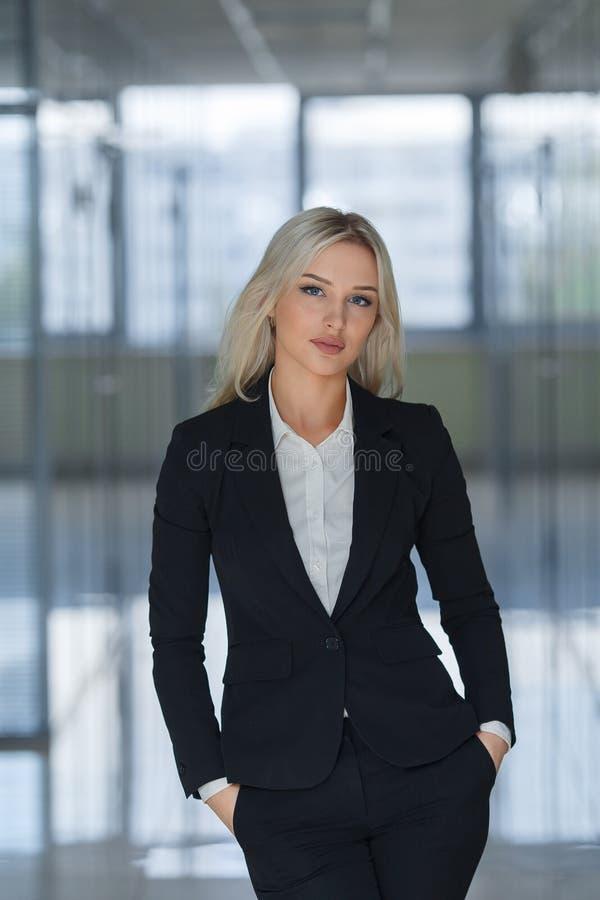 Jeune femme d'affaires sérieuse avec des mains dans des poches regardant l'appareil-photo photographie stock libre de droits