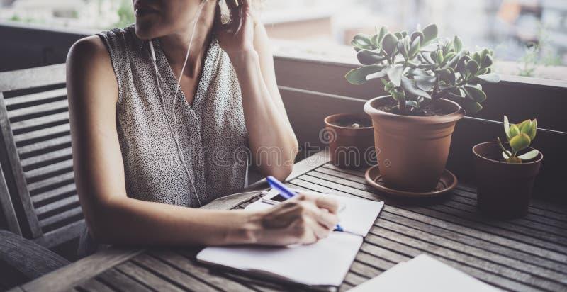 Jeune femme d'affaires s'asseyant à la table dans la terrasse de caffee et prenant des notes dans le carnet Sur la table est le s photos stock