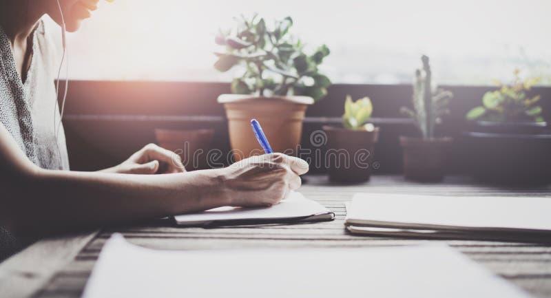 Jeune femme d'affaires s'asseyant à la table dans la terrasse de caffee et prenant des notes dans le carnet Sur la table est le s image libre de droits