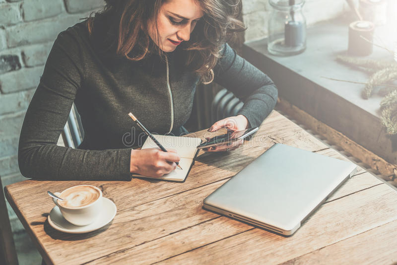 Jeune femme d'affaires s'asseyant à la table en bois dans le café et le smartphone d'utilisation tout en faisant des notes dans l photo libre de droits