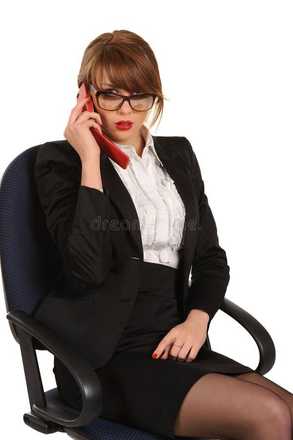 Jeune femme d'affaires s'asseyant dans la présidence de bureau images libres de droits