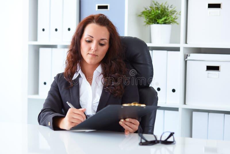 Jeune femme d'affaires s'asseyant derrière le bureau image stock