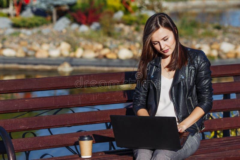 Jeune femme d'affaires s'asseyant et travaillant en parc avec l'ordinateur portable photographie stock libre de droits