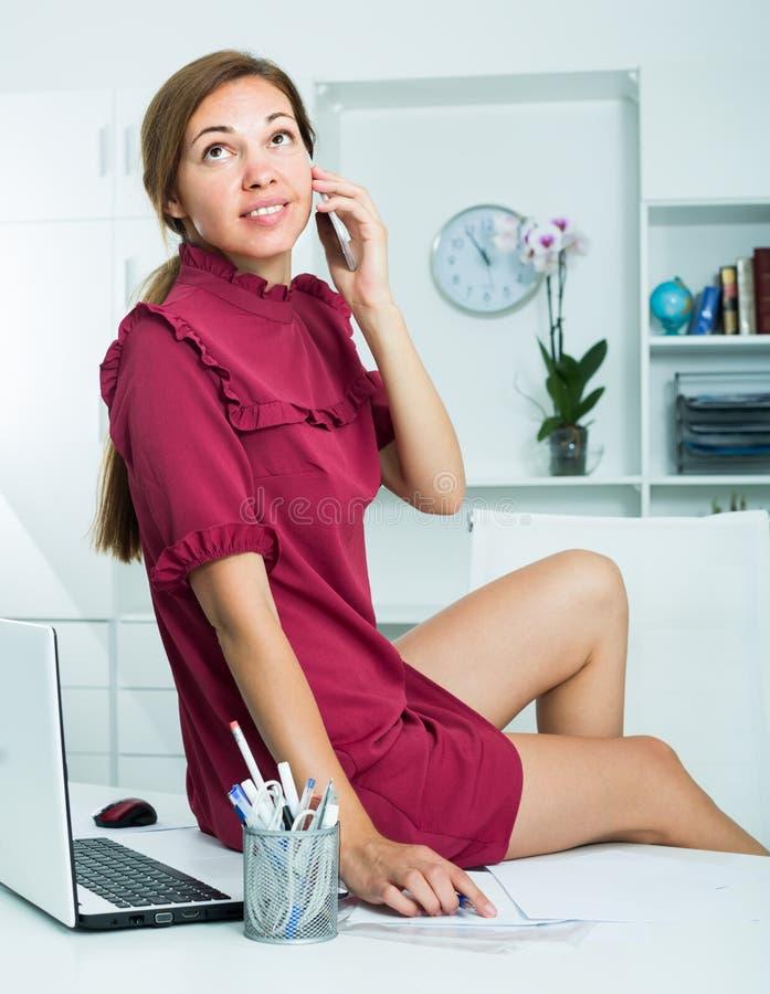 Jeune femme d'affaires s'asseyant sur le bureau fonctionnant au bureau images stock