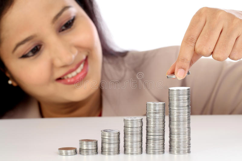 Jeune femme d'affaires s'chargeant de la pile de pièces de monnaie - escroquerie de croissance d'argent photographie stock libre de droits