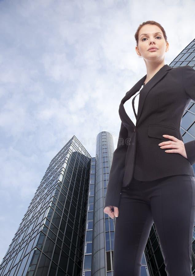 Jeune femme d'affaires se tenant devant l'immeuble de bureaux photographie stock