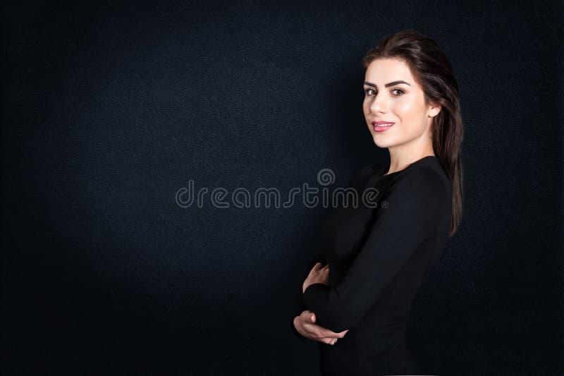 Jeune femme d'affaires se tenant sérieuse sur le fond noir photographie stock libre de droits