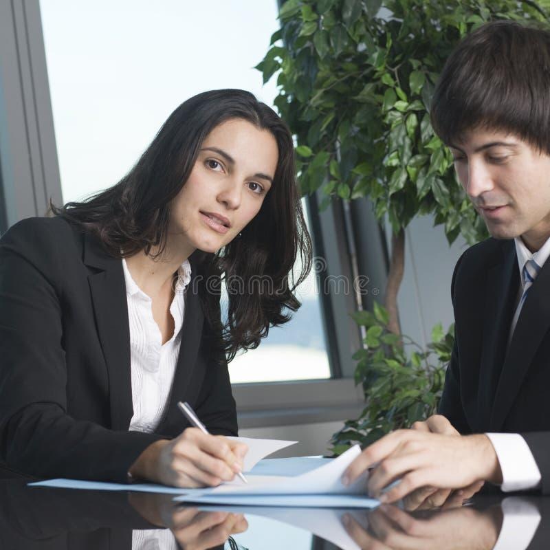 Jeune femme d'affaires signant quelques papiers photo libre de droits