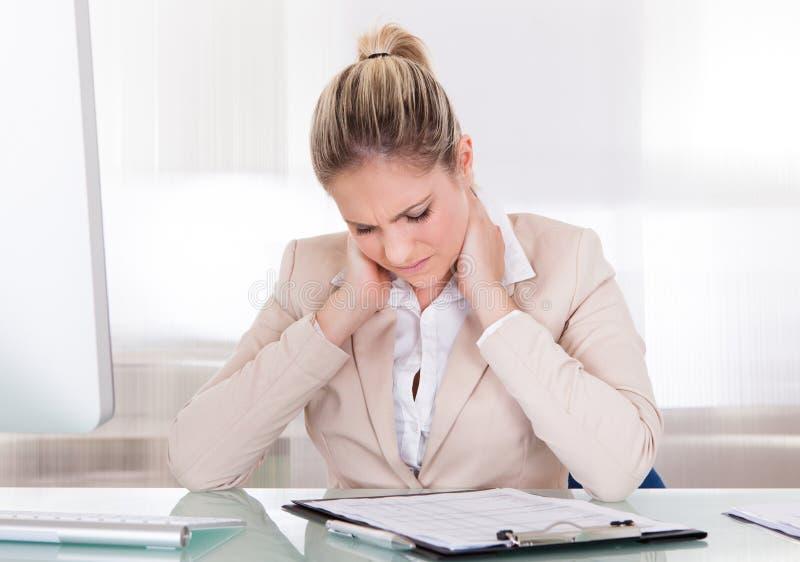 Jeune femme d'affaires souffrant de la douleur cervicale au bureau photos stock