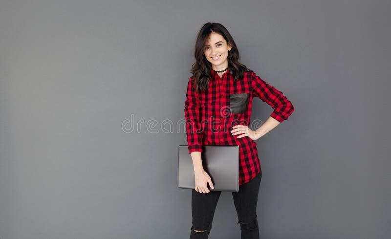 Jeune femme d'affaires souriant et tenant un ordinateur portable photo stock