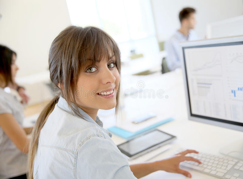 Jeune femme d'affaires sur l'ordinateur, collègues à l'arrière-plan photographie stock