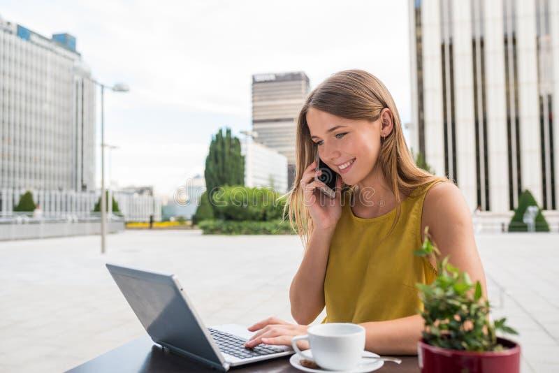 Jeune femme d'affaires sur l'ordinateur et au téléphone portable photographie stock libre de droits
