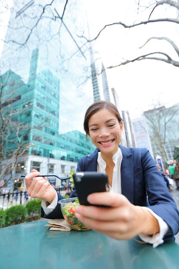 Jeune femme d'affaires sur le smartphone dans la pause de midi photographie stock