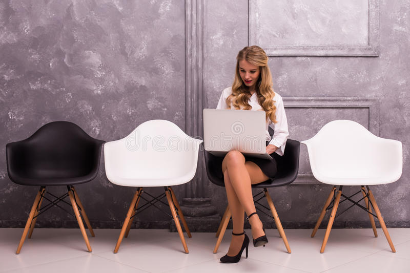 Jeune femme d'affaires tenant l'ordinateur portable tout en se reposant sur la chaise photographie stock