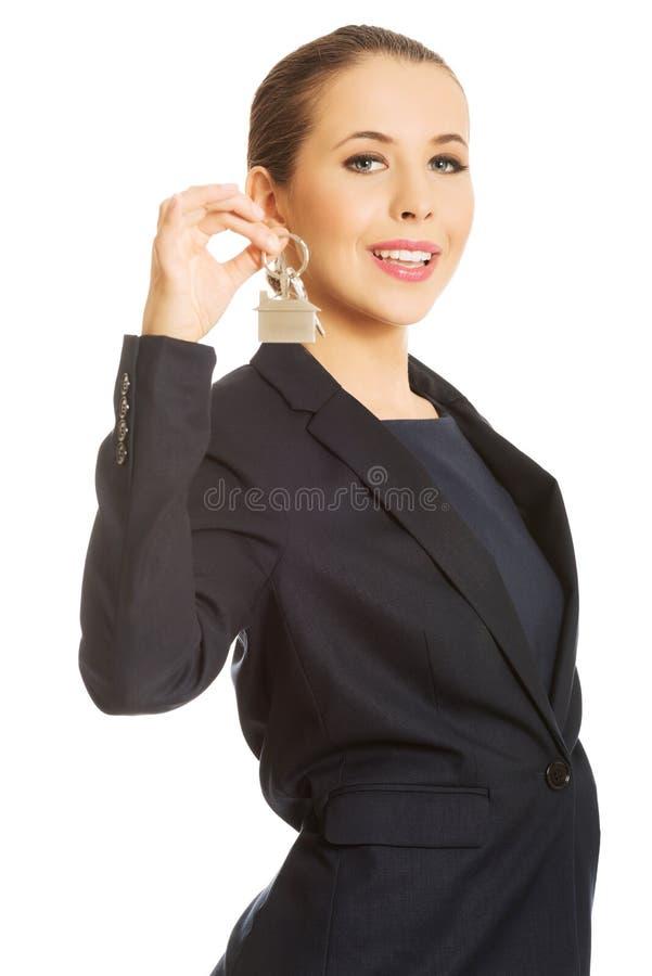 Jeune femme d'affaires tenant la clé de maison photo stock