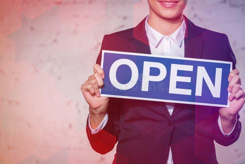 Jeune femme d'affaires tenant la plaquette ouverte de signe contre le mur de briques photos stock