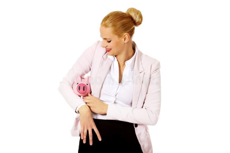 Jeune femme d'affaires tenant la tirelire photo stock