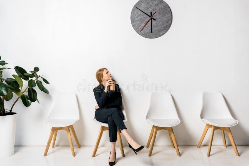 jeune femme d'affaires tenant le café pour aller regarder l'horloge tout en attendant photos stock