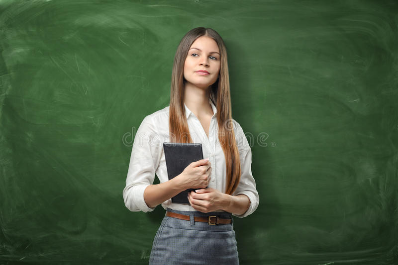 Jeune femme d'affaires tenant son dayplanner et pensant sur le fond vert de tableau images libres de droits
