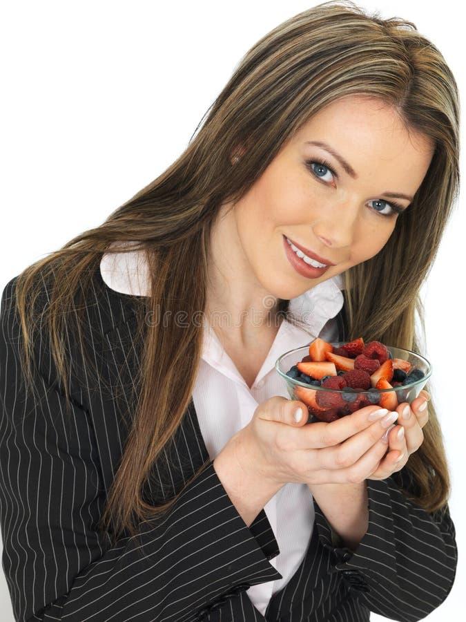 Jeune femme d'affaires tenant un bol de baies mélangées fraîches photo libre de droits