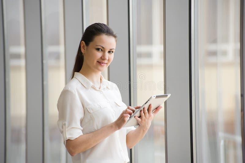 Jeune femme d'affaires travaillant à l'ipad tout en se tenant prêt la fenêtre dans le bureau Beau jeune modèle femelle dans le bu photographie stock
